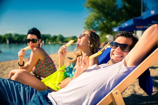 女と男のビーチでアイスクリームを食べる