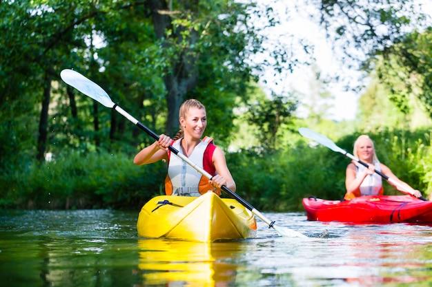 森の川でカヌーを漕ぐ女性