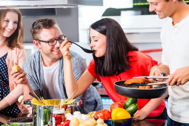 パスタと肉を国内の台所で料理をする友人