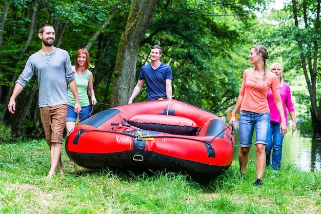 森の川にゴム製のボートを運ぶ友人