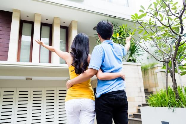 男は彼の女性に彼らの新しいアジアの家を見せる