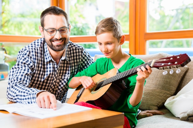 父と息子が自宅でギターを弾く