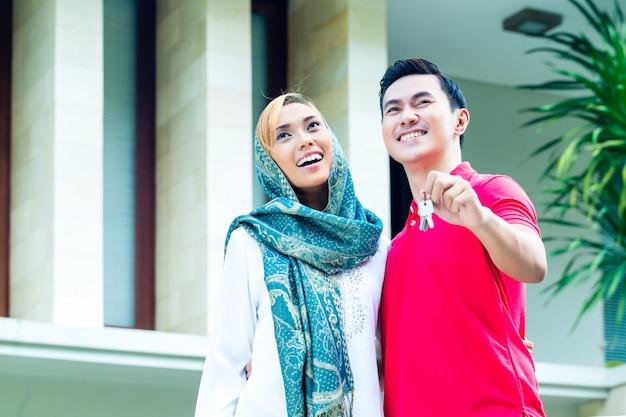 アジアのイスラム教徒のカップルが家に移動