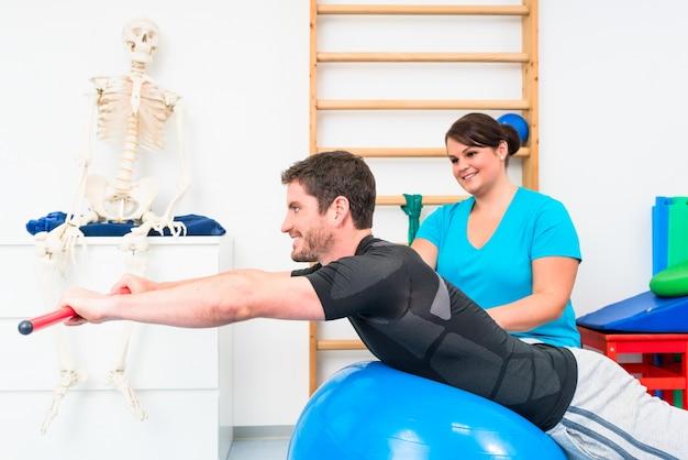 Молодой человек работает в физиотерапии на швейцарский мяч с гимнастической палкой