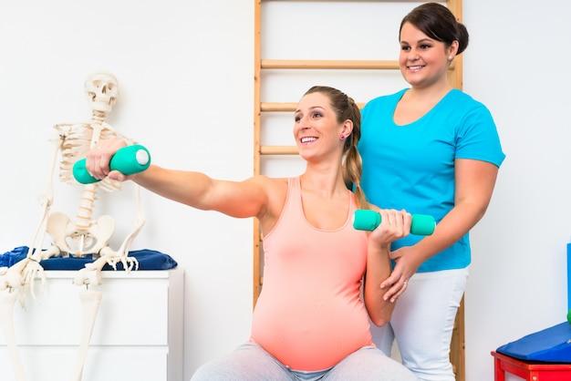 妊娠中の女性が理学療法でダンベルでワークアウト