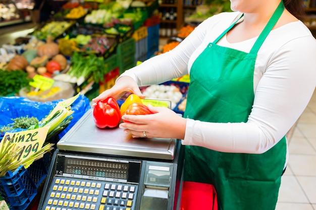 Продавщица взвешивает овощи на весах в бакалейной лавке
