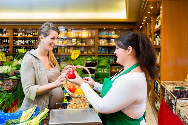 食料品店で女性に野菜を渡す販売婦人