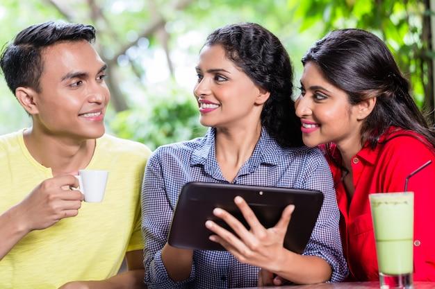 タブレットコンピューターを見て若いインド人のグループ