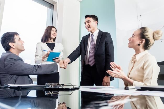 ビジネスマンは成功した取り引きの後で手を振る