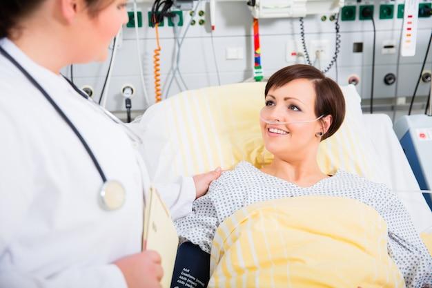 女性患者の結果をチェックする集中治療の医師