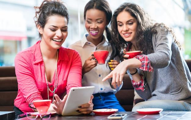Молодые женщины в кафе, принимая селфи