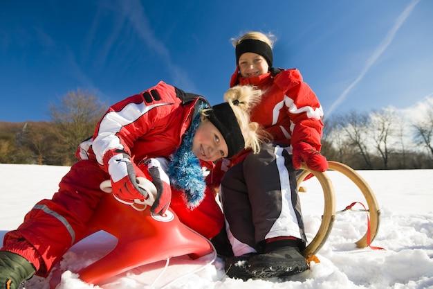 トボガンに雪の中で姉妹