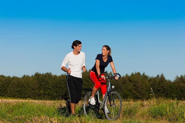 Молодая пара занимается бегом и велосипедом