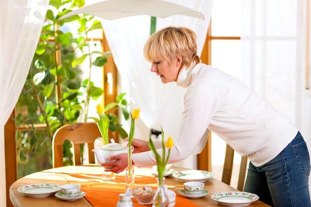 コーヒータイムの紅茶のテーブルを設定する女性