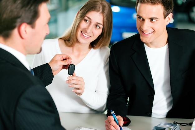 カップルが自動車販売店で売買契約を締結