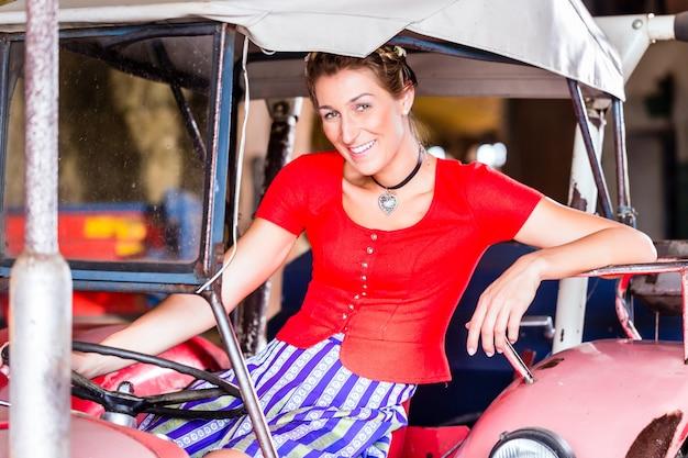 ディアンドルのドレスを運転するバイエルン女性のトラクター