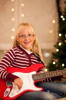 Девушка с гитарой перед елкой
