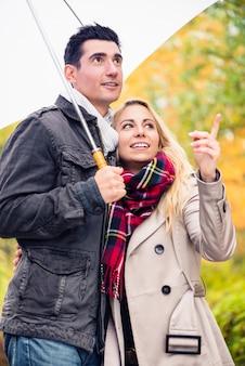 Пара наслаждается осенним днем, гуляя, несмотря на дождь