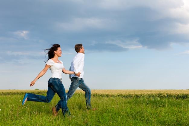 幸せなカップルが牧草地で実行されています。