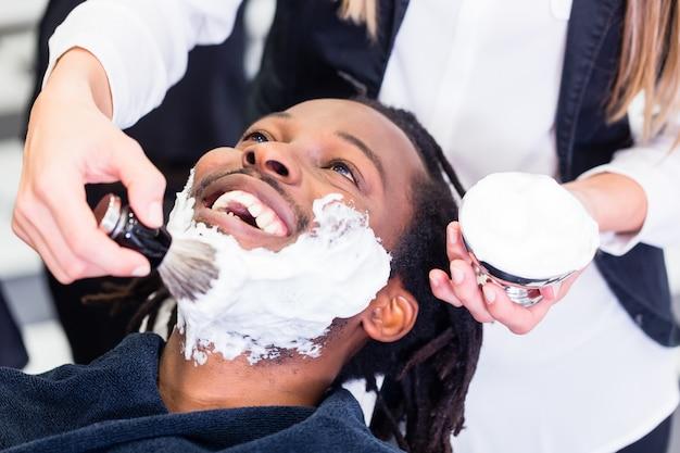 Клиент в парикмахерской с кремом для бритья