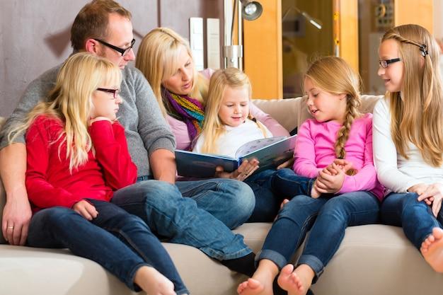 家族の家でソファの上の本で物語を読んで
