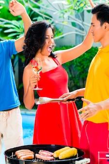 Азиатские друзья празднуют барбекю у бассейна