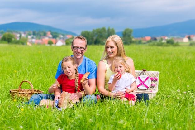 牧草地でピクニックを持つ幸せな家族