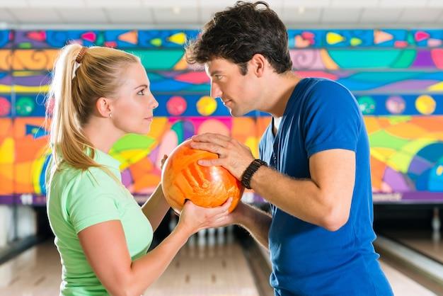 Молодые люди играют в боулинг и веселятся