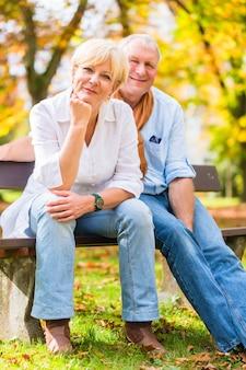 Пожилая пара сидит на скамейке осенью