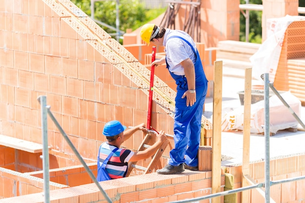 Рабочий проверяет стены на строительной площадке