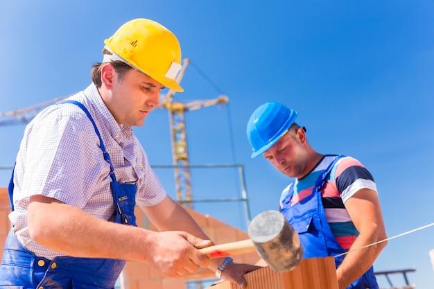 Строители строят стены дома