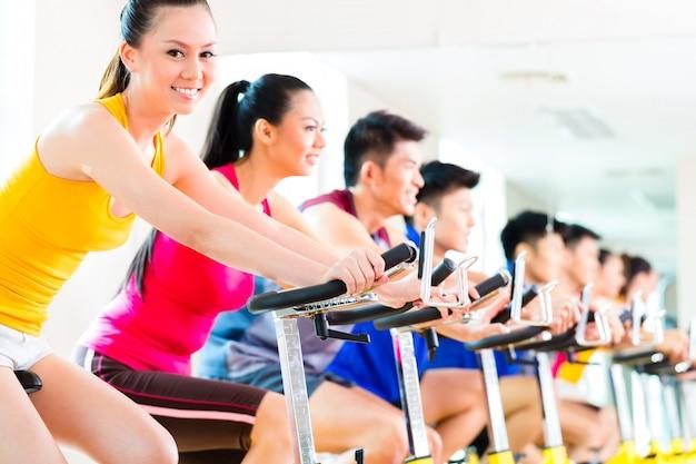 フィットネスジムで自転車の回転のトレーニングでアジアの人々