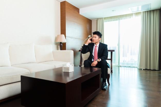Китайский бизнесмен в командировке в гостиничном номере