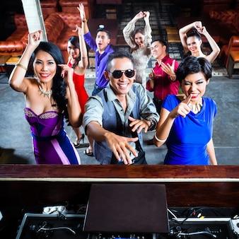 アジアの人々がナイトクラブのダンスフロアでパーティー