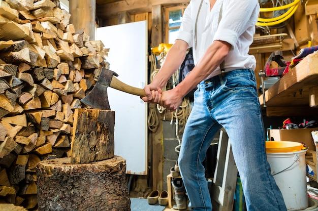 若い男が山のシャレーで薪を刻んで