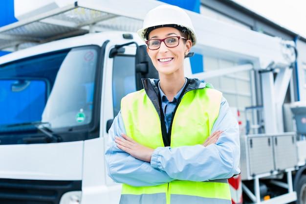 サイト上のトラックの前で女性エンジニア
