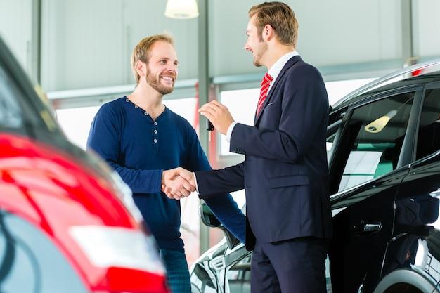 Молодой человек и продавец с авто в автосалоне