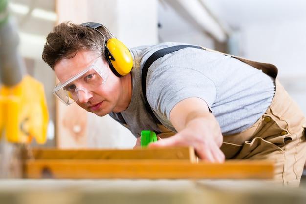 Плотник, использующий электрическую пилу в столярных изделиях