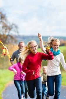 家族は凧揚げ秋の森で散歩します。