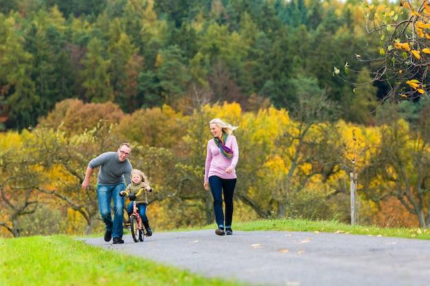 秋や秋の公園で自転車を学ぶ少女