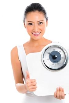 アジアの女性が体重計で体重を減らす