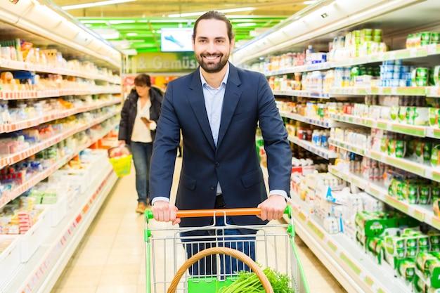 大型スーパーマーケットで買い物カゴを持つ男