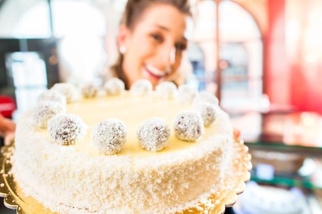 菓子屋でケーキを提示する女性のパン屋