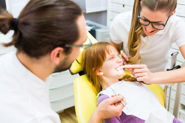 歯科手術で女の子治療を与える歯科医