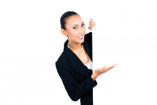 Азиатская коммерсантка показывая пустую белую доску
