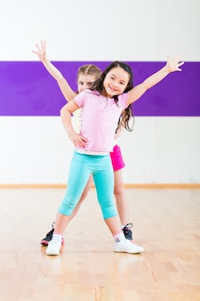 Дети тренируют фитнес в школе танцев