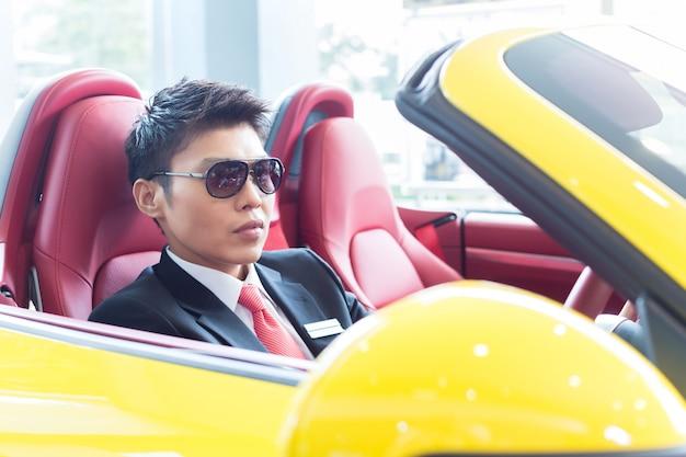 アジア人の男性が新しいスポーツカーをテスト