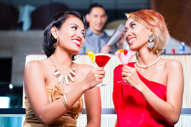 Азиатские женщины пьют коктейли в модном баре