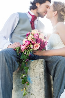 ブライダルペアの結婚式の後のフィールドにキス