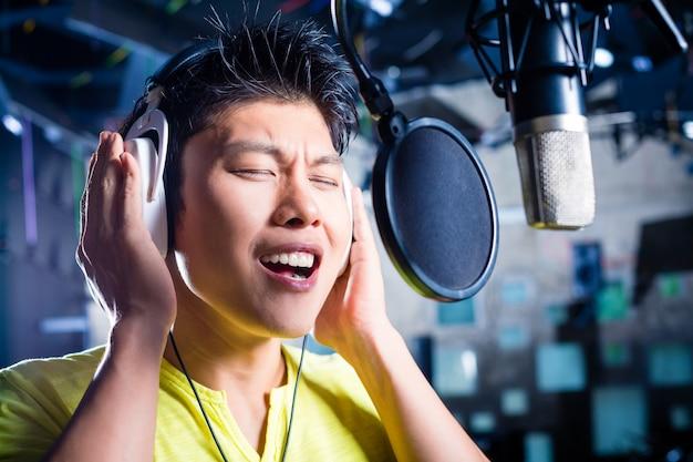 アジアの男性歌手がレコーディングスタジオで曲を制作